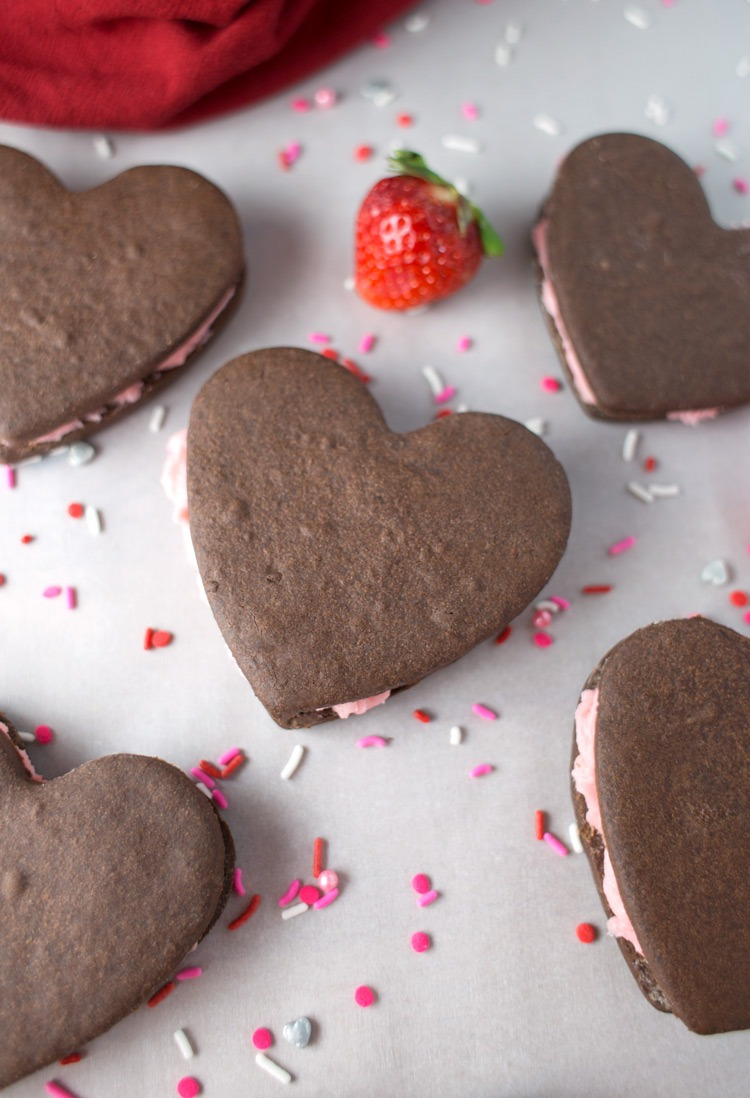 Chocolate Shortbread Strawberry Filled Cookies. Delicious chocolate shortbread cookies with a strawberry frosting, perfect for your Valentine's Day recipe plans! Get the full chocolate shortbread cookie recipe and filling info (and where to grab your heart-shaped cookie cutters!) by clicking through! | SeasonlyCreations.com | @SeasonlyBlog